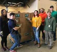Students stand in front of a large pallet of boxes for donation. Click to learn more about community service.
