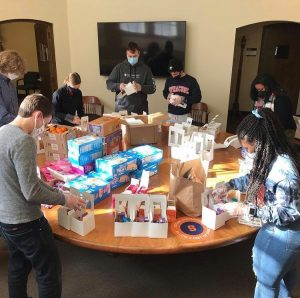 A student religious group stands around a table packing care packages