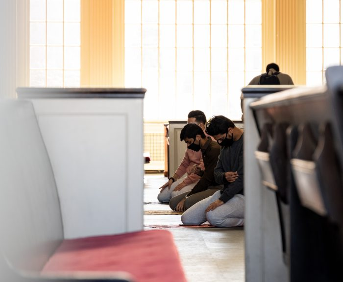 Three students kneeling with heads bowed in prayer