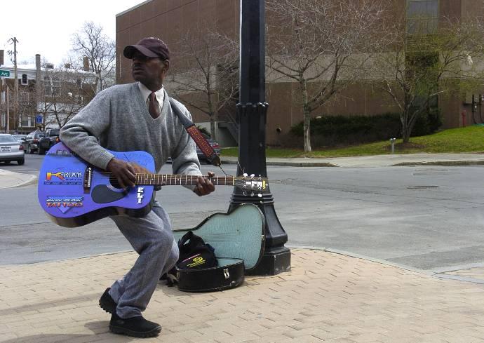 Eli Harris playing a guitar on a sidewalk